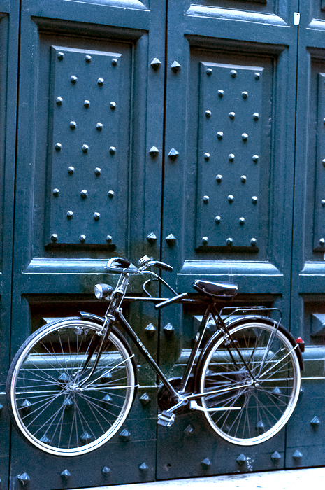 A bicycle is suspended by it's lock to giant green studded doors outside the Campo de Fiori in Rome, Italy.