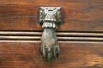 A woman's delicate hand is a whimsical brass door knocker in San Severino delle Marche.